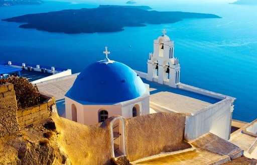 Blue domed chapels in Santorini, white buildings overlooking the sea