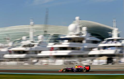 Car on Yas Marina racetrack goes past superyachts lined up at berth during Abu Dhabi Grand Prix