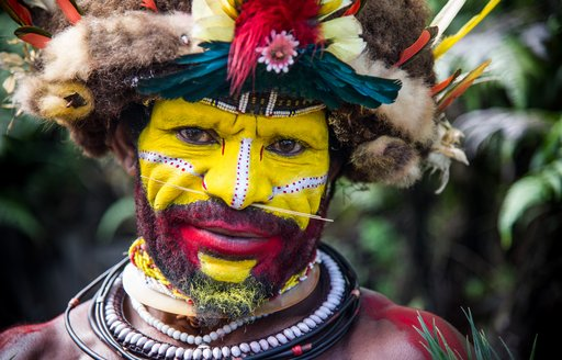 Man in face paint in Papua New Guinea showing off the country's authentic tribal culture