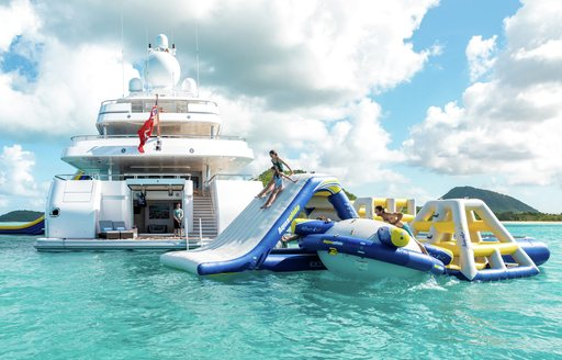 inflatable water park and obstacle course in the sea in thailand with view of lurssen motor yacht titania in background