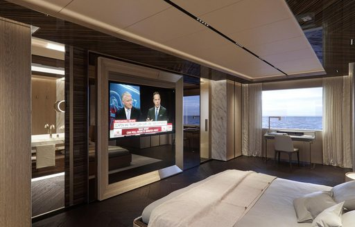 the large flat screen tv inside the master cabin of motor yacht geco with the windows wide open looking outtowards the ocean