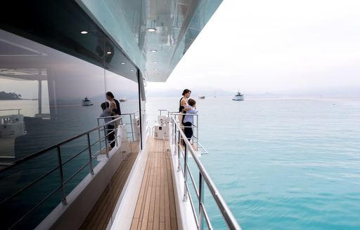 guests look out over the balcony on the sidedeck of motor yacht ONEWORLD