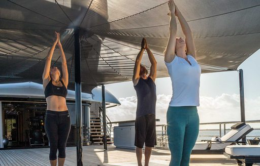 Charter guests do yoga session on the aft deck of a megayacht