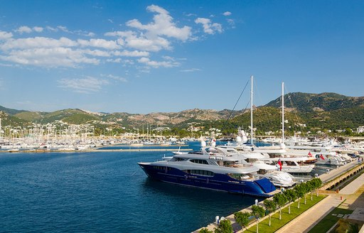 Yachts berthed in a marina beneath blue skies