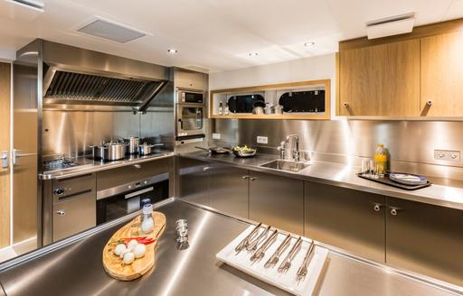Stainless steel galley of Game Changer yacht with knives and food being prepared in foreground