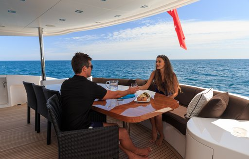 Charter guests enjoy a drink on aft deck alfresco dining area on board motor yacht Paradise