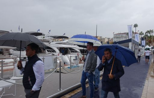 People at Cannes Yachting Festival 2020 covering below umbrellas