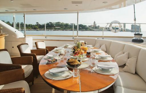 Dining set up onboard Parsifal III, external rounded sofa and large dining table accompanied by four armchairs, overlooking sea and distant palms