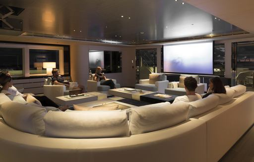 guests watch a movie in the games room aboard motor yacht NAUTILUS