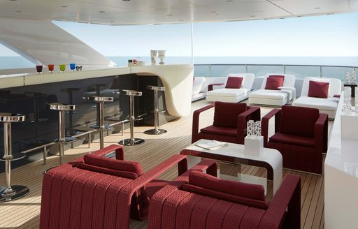 Al fresco seating onboard Charter yacht HOME, shaded armchairs and coffee tables adjacent to long bar with stools, surrounded by sea