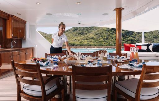 crew fixes place setting on table of superyacht