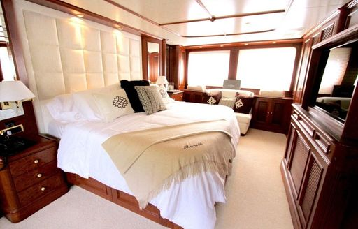 master suite with neutral coloured furnishings and rich wood joinery on board superyacht BRUNELLO