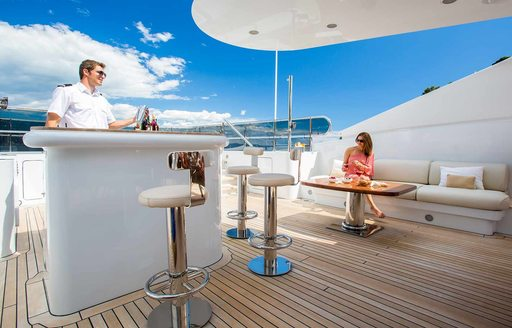 Sundeck of superyacht DIANE, with charter guest enjoying cocktail