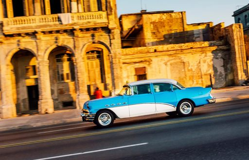 A classic 1950s car cruises down Cuban street lined with colonial buildings