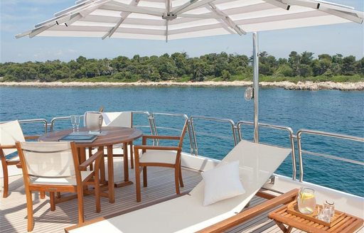 Sun deck view of table and sun loungers on board luxury yacht BRUNELLO