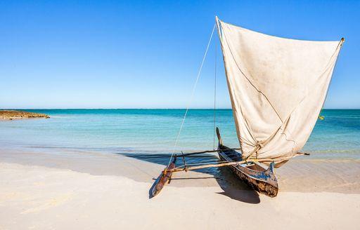 A small sailing canoe on the shore