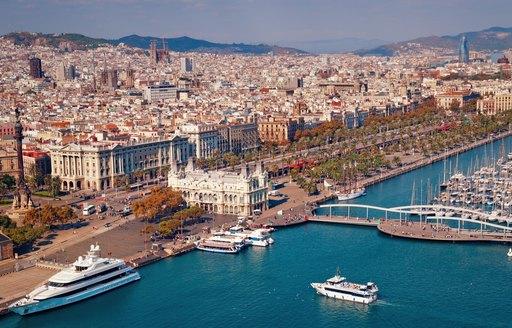 Barcelona skyline, Sagrada Familia, superyachts and Torre Agbar are visible