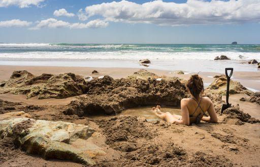 women bathes in pool of hot water on Hot Water Beach on Coromandel peninsula in New Zealand