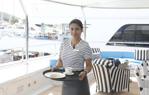 yacht stew holds tray during antigua charter show