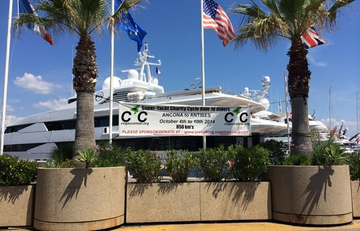 International Yacht Club of Antibes cogs for cancer sign next to superyachts in french riviera harbour