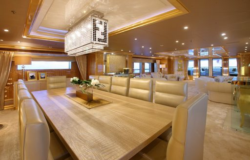 dining area with lounge beyond in main salon of luxury yacht 'Lady Luck'