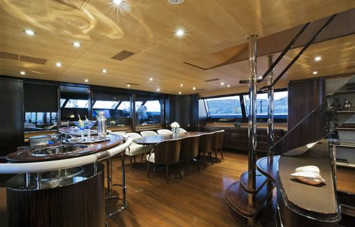 Interior dining area onboard superyacht Parsifal III. Adjoined by wet bar and suitcase, overlooking wide stretching windows.