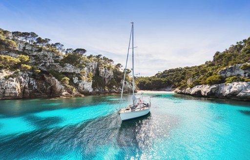 little sailing boat sits in small cove in the balearic islands, surrounded by rocks and forest