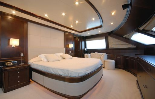 elegantly styled master suite with dark wood and light coloured upholstery aboard charter yacht 'Elena Nueve'