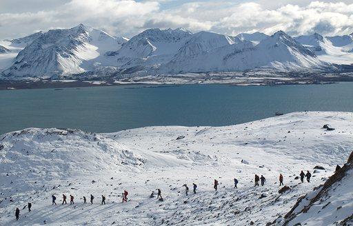 snowy terrains in norway, with hikers walking across