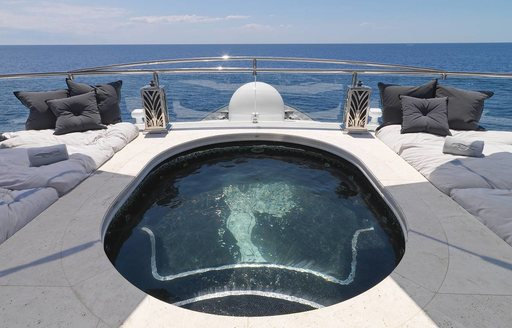 mosaic-lined swimming pool surrounded by sand-blasted travertino on sundeck of motor yacht Silver Angel