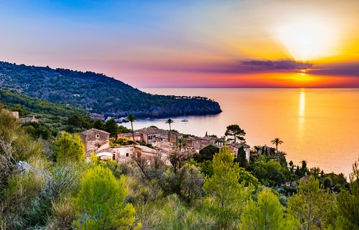 Sunset over sea in Majorca, with small village in foreground and water stretching out to horizon