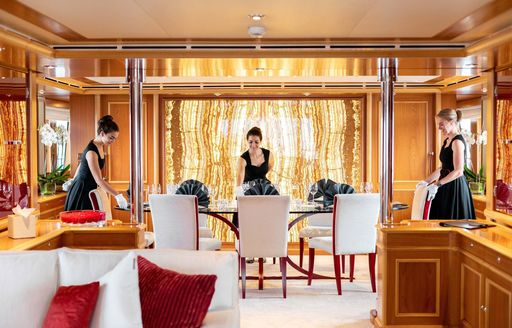 luxury yacht crew make table in dining salon