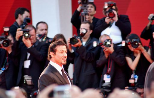 A leading man faces cameras on the red carpet wearing a black suite and red tie at the Venice Film Festival