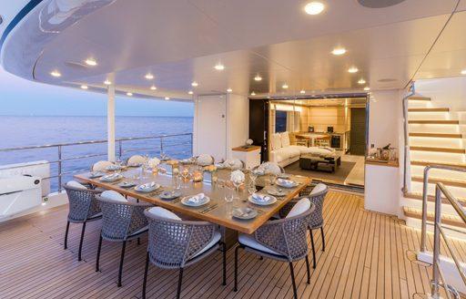 table set for dinner on upper deck aft of charter yacht NARVALO