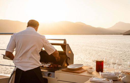 chef makes food on barbecue on superyacht