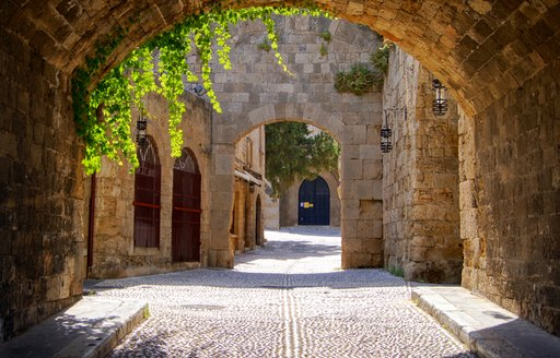 cobbled stone street in greece with ivy hanging over door archway