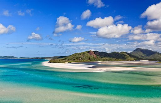 white sandy beach backed by forest and surrounded by turquoise waters in the Great Barrier Reef