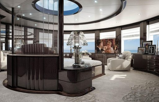Charter yacht SPECTRE owners suite with grey carpets, black bed frame, skylight and glass furnishings. Great Gatsby on TV screen