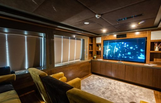 Cineam room on luxury charter yacht ARESTEAS with comfy chairs lined up infront of wide screen TV
