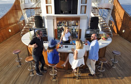 Charter guests around the alfresco bar on superyacht Christina O