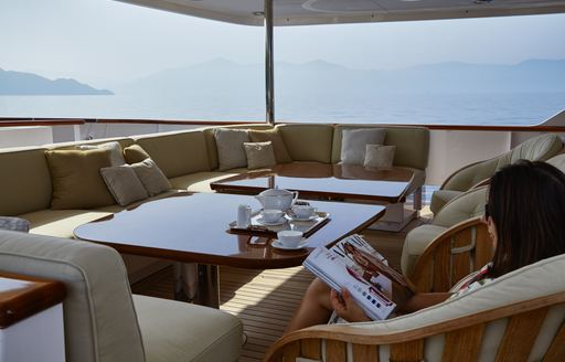 charter guest reads a magazine on the aft deck of charter yacht ANCALLIA