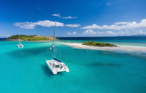 luxury catamaran on a private charter anchors at Sandy Spit in the British Virgin Islands