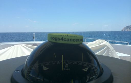 cogs for cancer wristband sitting on compass from navigation area of huge superyacht cruising in the Mediterranean