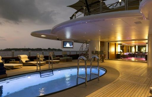 Swimming pool and sun loungers on exterior deck of yacht charter NIRVANA. Glimpse of interior main deck visible in background.
