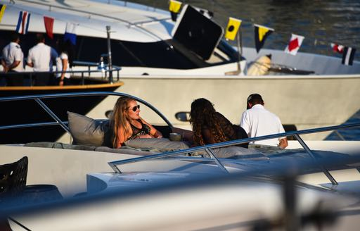 Women recline on sunpads on a yacht while looking out at F1 Monaco Grand Prix
