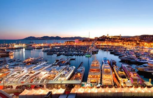 A collection of yachts berthed in Cannes at night for the film festival