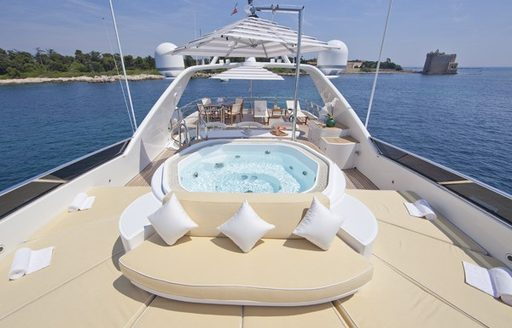 Sun deck of motor yacht BRUNELLO with sun pads and spa pool in foreground