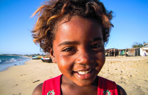 A young black child with amber hair smiles into the camera
