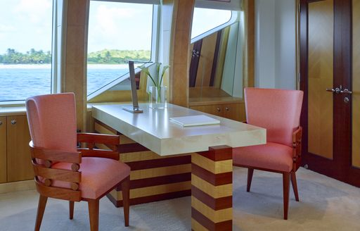 Table and chair onboard Victoria Del Mar with plant on table and windows looking out to sea
