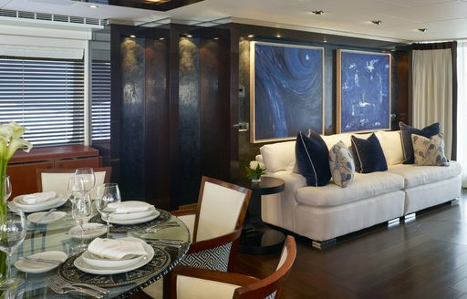 glass-topped dining table and cream sofa in the main salon aboard superyacht ROCKET